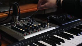 Music producer engineer turns knobs on mixing board with equalizer. Home studio recording mixing and mastering process. Electronic. Midi piano and mixing board stock video