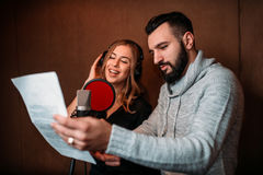 Music producer and female singer in headphones. Music producer shows text to female singer in headphones, song record in music studio. Female singer recording Stock Photography
