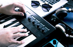 Music producer is producing on synthesizer keyboard royalty free stock image