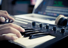 Music producer is working with Synthesizer. And laptop stock photography