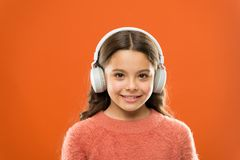 Music produces pleasure. Perfect sound stereo headphones. Girl cute little child wear headphones listen music. Kid. Listen music orange background. Recommended stock image