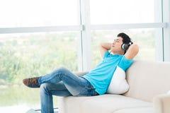 Music relaxation. Horizontal image of a man enjoying music in headphones stock image