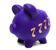 Music Savings. Purple colored piggy bank with gold colored music notes representing musical savings stock image