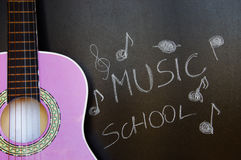 Music school of guitar for children. Music school for children with purple guitar closeup on blackboard background Royalty Free Stock Image
