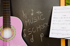 Music school of guitar for children. Music school for children with purple guitar closeup on blackboard background and music sheets Stock Images