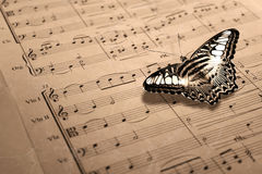 Music score with butterfly. A close-up shot of an old music shore with a butterfly stock photos