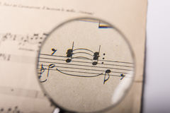 A music score. View of the notes in a music score through a magnifying lens Royalty Free Stock Photos