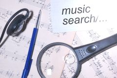 Music search.The two pieces of the score notes, magnifying glass. Ballpoint pen, headphones. Different music for everyone stock photography
