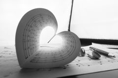 Music series in the form of heart. A sheet of white paper with printed thereon music notes on a table Royalty Free Stock Photo