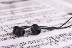 Music sheet with headphones. Photo of printed Music sheet and headphones Stock Photo