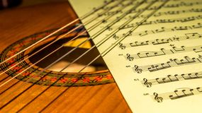 Music sheet between strings and sound hole of a acoustic guitar. royalty free stock photography