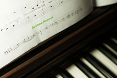 Music sheets and piano. Keyboard  in the background Stock Image