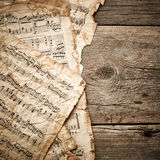 Music sheets. Vintage music sheets on wooden background Stock Photos