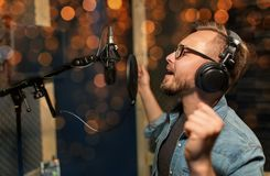Man with headphones singing at recording studio. Music, show business, people and voice concept - male singer with headphones and microphone singing song at stock photo