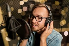 Man with headphones singing at recording studio. Music, show business, people and voice concept - male singer with headphones and microphone singing song at Stock Images