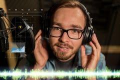 Man with headphones singing at recording studio Stock Photo