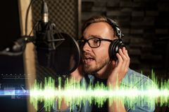 Man with headphones singing at recording studio Stock Photography