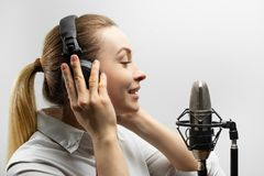 Music, show business, people and voice concept - singer with headphones and microphone singing a song in recording studio, stock photos