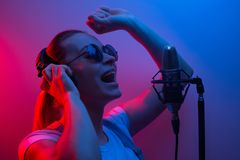 Music, show business, people and the voice of a singer or DJ with headphones with glasses and a microphone singing a song in the stock photo