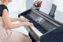 Music. Side view of woman playing piano, body and buttons of the piano were digitally modified Stock Photo