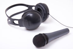 Music and sound concept - close up of microphone and headphones Royalty Free Stock Images