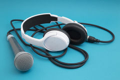 Music and sound. Microphone, headphones and cable on a blue background royalty free stock images