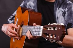 Closeup of man playing acoustic guitar. Music, sound, passion concept. Man playing on acoustic guitar, studio shot, black background Royalty Free Stock Photography