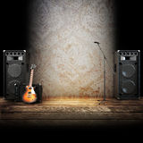 Music stage or singing background. Microphone, guitar and speakers with wood flooring. Advertising concept with room for text or copy space Stock Image