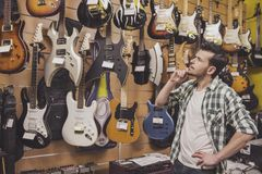 Music store. Young man is considering electric guitars music store stock photos
