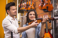 Music store. Young men is teaching girl to play the violin at the music store Stock Image