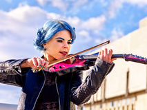 Music street performers with girl violinist. Beautiful music street performers girl violinist with blue hair playing  aganist sky with clouds outdoor Stock Image