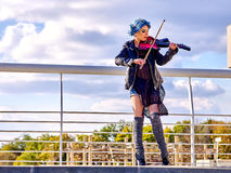 Music street performers with girl violinist. Music street performers girl violinist with blue hair playing  aganist sky with clouds outdoor. Freedom concept Royalty Free Stock Photo