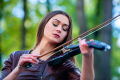Music street performers with girl violinist. Music street performers girl violinist  playing  in spring park outdoor. Violin music nature Royalty Free Stock Image