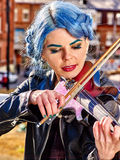 Music street performers with girl violinist. Portrait of music street performers girl violinist with blue hair playing  aganist sky with city outdoor Royalty Free Stock Images