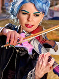 Music street performers with girl violinist. Portrait of music street performers girl violinist with blue hair playing  outdoor Royalty Free Stock Photography