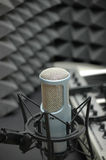 Music Studio. Microphone with keyboard and earphones. Acoustic sound panels in the background Stock Images