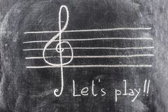 Sol key on pentagram sketched on blackboard. The music symbol of Sol key is sketched on the pentagram, with white chalk on the blackboard. The write Let`s play royalty free stock image