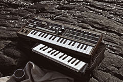 Music synthesizer lying on rocks Stock Image