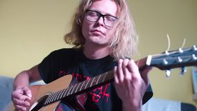 Music teacher with glasses playing an acoustic guitar. A music teacher, with glasses, with long hair, plays an acoustic guitar stock footage