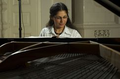 Music Teacher And Grand Piano. Portrait of a female piano teacher looking downward as she plays grand piano.  Taken from across open piano top Stock Photography