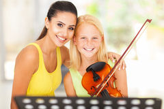 Music teacher student. Beautiful music teacher with young violin student Royalty Free Stock Photos
