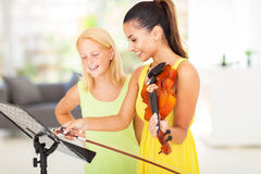 Music teacher student. Pretty music teacher pointing notes to her student Stock Image
