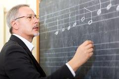 Music teacher. Writing on the chalkboard stock photography