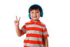 Music and technology concept.Little boy with headphone showing victory gesture. Music and technology concept.Asian little boy with headphone showing two fingers Stock Photos