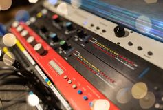Close up of music mixing console. Music, technology, electronics and equipment concept - close up of mixing console at sound recording studio over lights Royalty Free Stock Photography