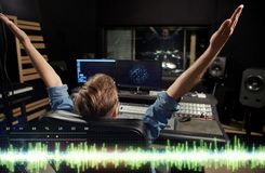 Man at mixing console in music recording studio. Music, technology, people and equipment concept - happy man at mixing console in sound recording studio Royalty Free Stock Image
