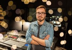 Man at mixing console in music recording studio. Music, technology, people and equipment concept - happy smiling man at mixing console in sound recording studio Royalty Free Stock Photo