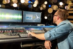Man at mixing console in music recording studio. Music, technology, people and equipment concept - man at mixing console with computer monitors in sound Royalty Free Stock Photo