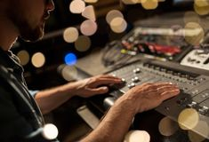 Man using mixing console in music recording studio. Music, technology, people and equipment concept - man using mixing console in sound recording studio over stock image