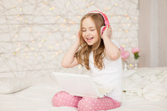 Music and technology. Portrait of young girl in pajamas with white laptop and wireless pink headphones, sing song on Stock Photos